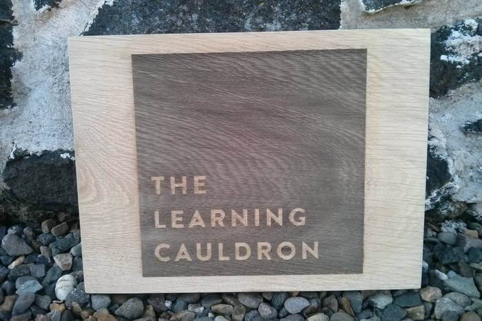 The Learning Cauldron oak sign