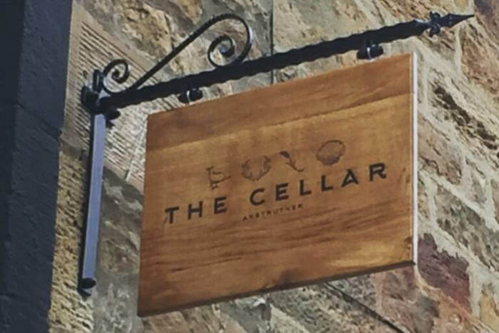 Oak sign for The Cellar Restaurant