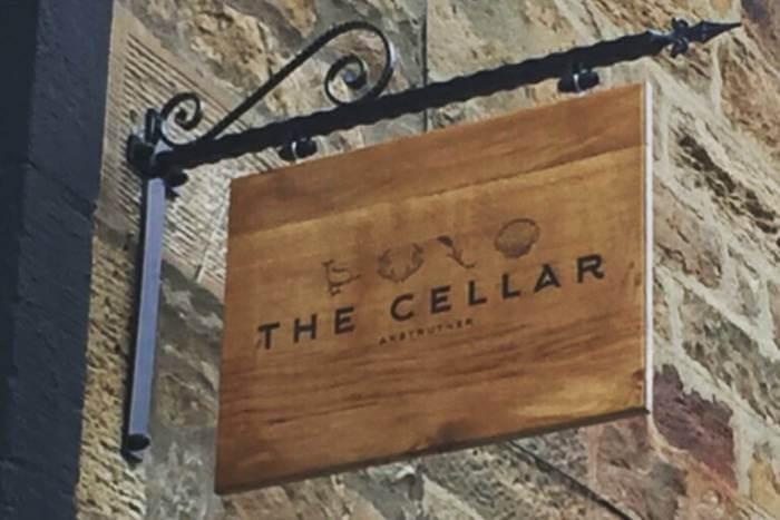 Oak sign for The Cellar Restaurant